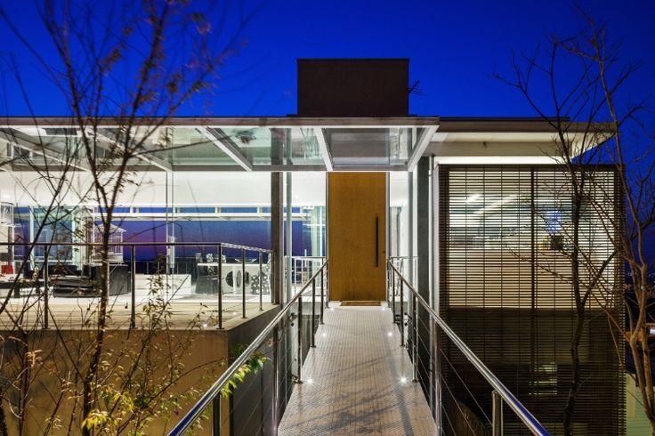A entrada da Casa Jatobá, projetada pelo escritório Gesto Arquitetura, é marcada pela passarela metálica. Com piso em chapa galvanizada, como as usadas em ônibus, ela dá acesso para ala social - com estar e jantar, à esquerda - e para os dormitórios, à direita