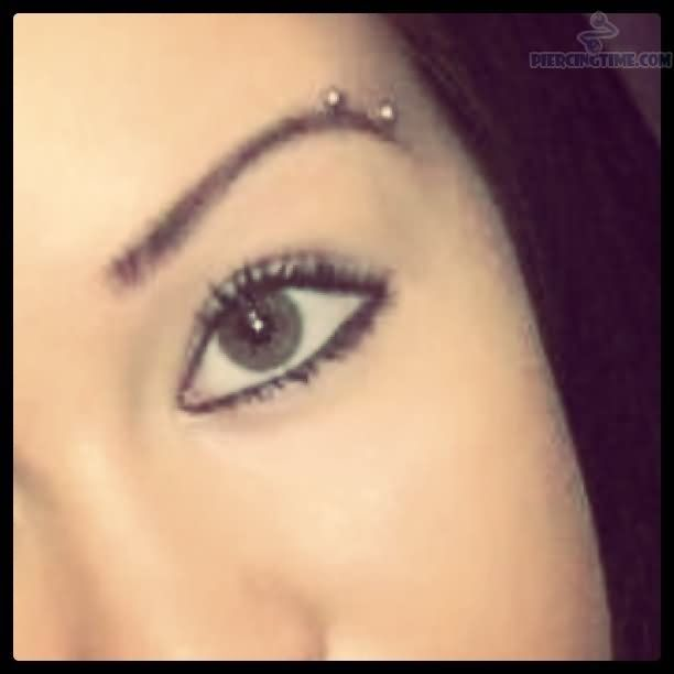Tasteful horizontal eyebrow piercing with small stud