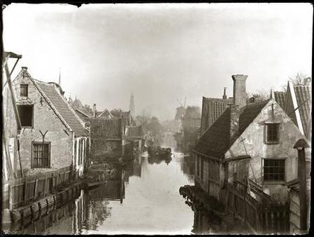 ...Bleekersloot,1890   Vijf jaar nadat Olie deze foto nam, werd hier de De Clercqstraat aangelegd. Op de achtergrond de Westertoren en de in 1898 afgebroken molen