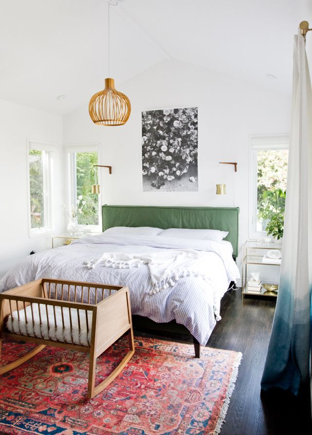 Colorful midcentury modern bedroom with a pink rug, green headboard and brass wall sconces.
