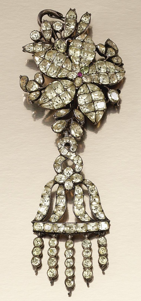 SILVER, CHRYSOBERYL AND RUBY PENDANT, PORTUGUESE SECOND HALF OF THE 18TH CENTURY.  Of stylised flower head design decorated with foil backed mixed-cut chrysoberyl, highlighted by a circular-cut ruby, to surrounds of foliage and suspending an articulated open work tassel set with mixed-cut chrysoberyl, later brooch fitting, original unusually shaped tooled leather fitted case.