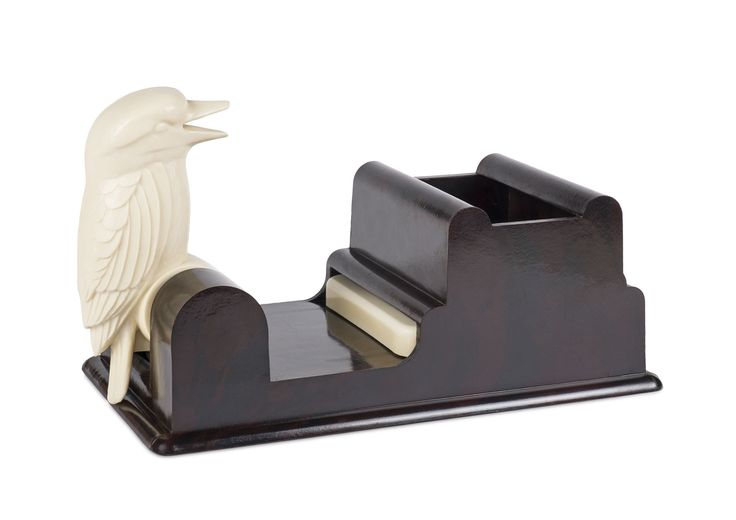 Kookaburra Cigarette Dispenser (c1950). This is an unusual curiosity made of bakelite. To use it, you would fill up the container section with cigarettes, and push the kookaburra down with a finger, as you do so the white tray moves out with a single cigarette in it. When the beak reaches the tray it will pick up a cigarette in it's beak and pop back up again. I guess it beats opening a packet to get a cig, but interesting bit of history anyway.