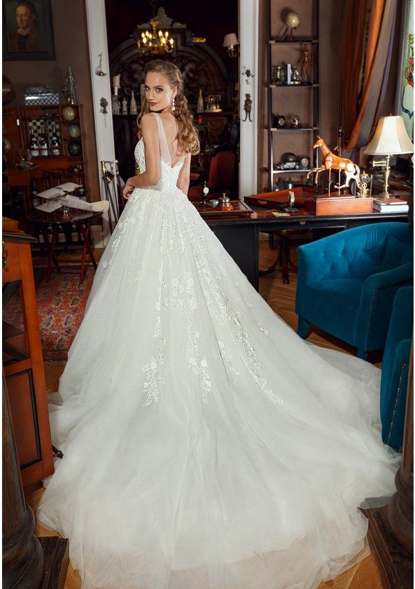 Wedding dress made of lace and tulle Embroidered with lace and manual beads application Princess silhouette, sweetheart neckline and cups included Open back and long cathedral train Skirt made of tulle layers with hand embroidery applications Closes in the back with zipper