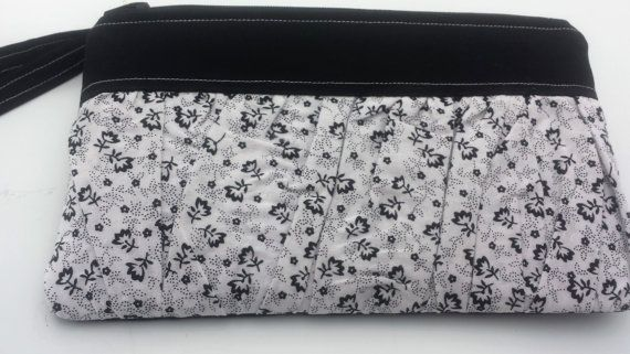 This stylish wristlet with a pleated front section is the perfect size to take on the go when you dont want to carry your heavy purse. Great for summer outings and parties as an evening bag! It holds all the essentials - your phone, keys, credit cards, small cosmetics and make up, cash, even a small point and shoot camera! The top and back of the Clutch is a subtle white on white chic floral patterned linen, with pale pink decorative top stitching, and the main ruffle on the front is a…