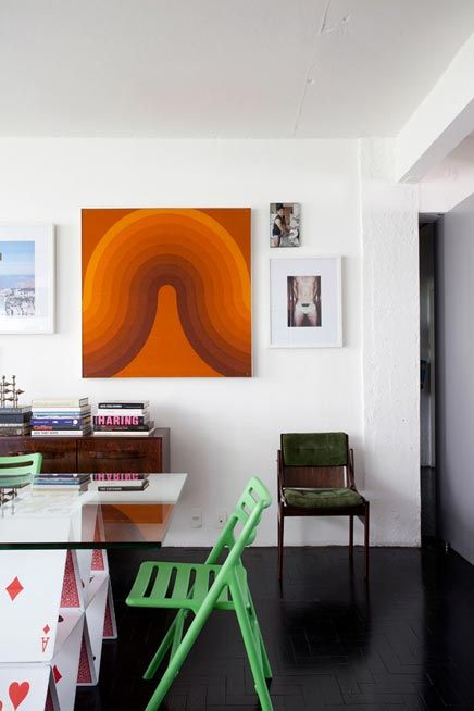 Apartment interior design in classic mid century style another view from dining chairs and glass dining table with big painting