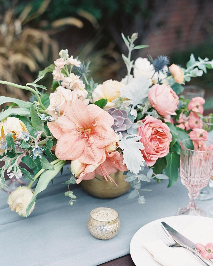 A gorgeous feminine floral centrepiece for your wedding, mixing soft green foliage with peach and pink blooms in beautiful style! Plus colour coordinated table decor and a glimmering golden vase. Beautiful!