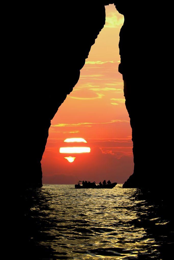 Ondergaande zon, doorgang, donker water.