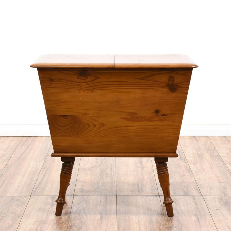 This country chic sewing cabinet is featured in a solid wood with a rustic pine finish. This cabinet end table has slanted sides, carved tapered legs and a large interior cabinet with 2 lift up tops. Unique storage piece perfect for knitting and sewing supplies! #americantraditional #storage #cabinet #sandiegovintage #vintagefurniture