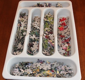 Using a flatware drawer tray as a creative way to store puzzle pieces while working on a puzzle. The different sections can be used for your groups of pieces. In this case, pieces were sorted by color.