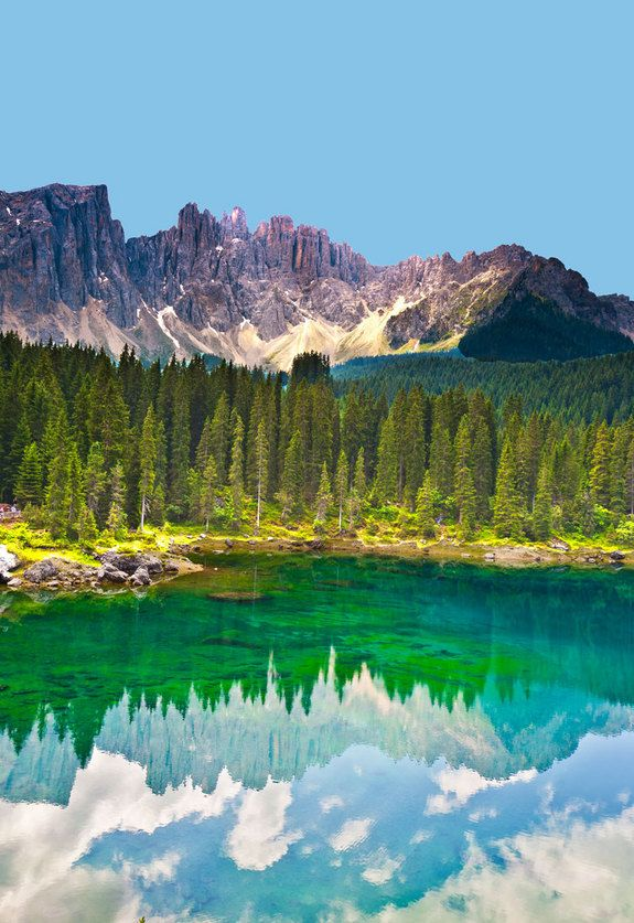 The crystal clear water of this lake,nestled by the Dolomites mountain range of north-eastern Italy allows the electric-green algae at its bottom to show through to the surface. absolutely gorgeous