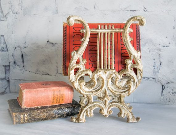 Beautiful piece holds paper goods: newspapers, books, magazines... in the shape of a lyre harp. It is made of cast iron and painted antique white with gold accent. It measures approximately 11 tall by 8 wide by 6 deep. Gorgeous french country look and would be perfect for your space.  (INTERNATIONAL SHIPPING PLZ CONVO FOR PRICE)