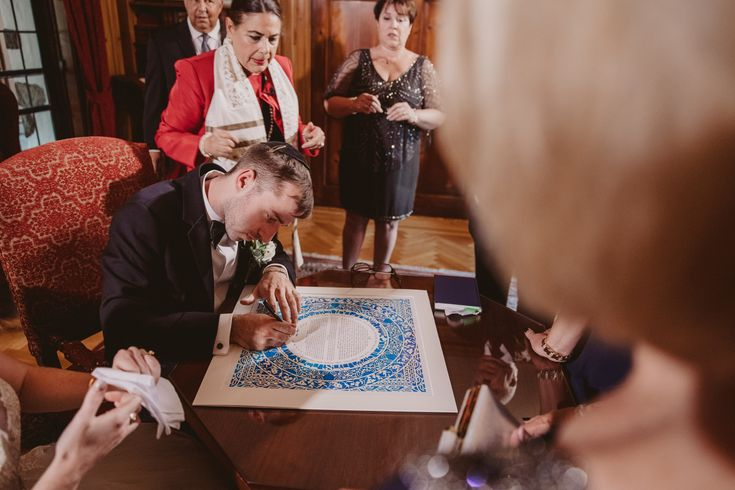 Ilyssa shared these gorgeous shots from her and Corey's Wedding 📸by @mattstallonephotography  the couple signing the Sasson Papercut - Light Blue Violet Ketubah surrounded by loving family and friends