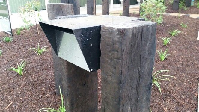 Recycled railway sleepers used as a feature posts and letterbox through this native garden in Brisbane.