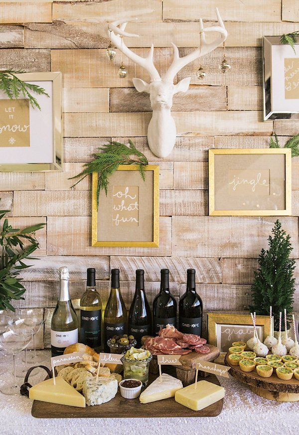 modern gold and white food table and wine bar with cheese and wine platter and a white deer head