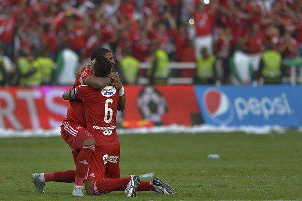 America de Cali's team players Camilo Ayala (L) and Juan Angulo celebrate after defeating Deportes Quindio in a Colombian Professional Football tournament promotion match in Cali, Colombia, on November 27, 2016. America de Cali defeated Deportes Quindio by 2-1 and returned to first division after five years. / AFP / LUIS ROBAYO