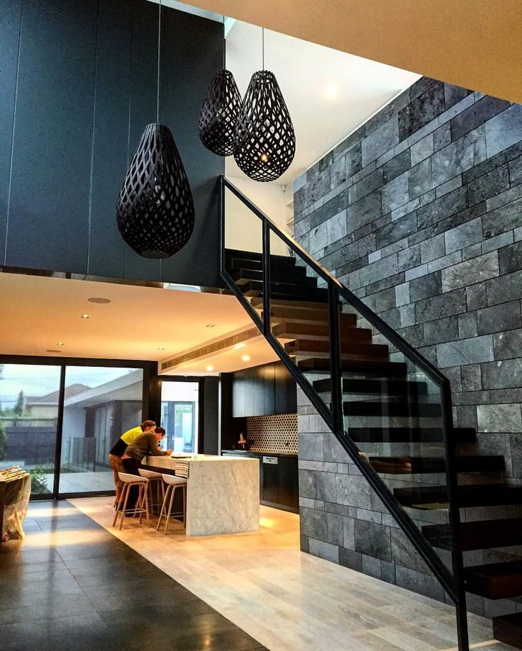 Striking black Koura pendants sitting pretty in this modern, architectural house. Loving the combination of textures and colours in this space! Shop the full range of David Trubridge pendant lights on our website now! www.lightworksonline.com.au