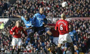 Shaun Goater beats his team-mate Nicolas Anelka to the ball to head in Manchester City's equaliser against Manchester United at Old Trafford in 2003.