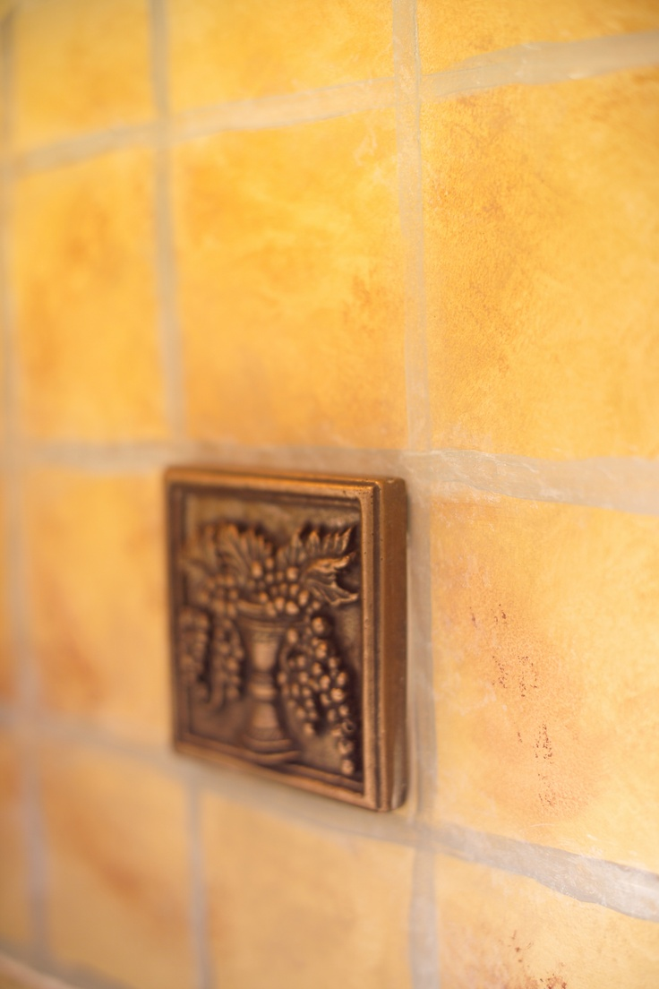 """Kelly has a friend that is an artist that """"painted"""" tile onto the walls.  Actual decorative tiles were added here and there to add drama and interest.  The backsplash is illuminated with a flourescent undercabinet light rated as """"warm"""" light - giving a glow like a traditional incandescent bulb."""