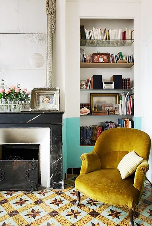 Floor tiles + vintage armchair + painted wall + fireplace + antique mirror