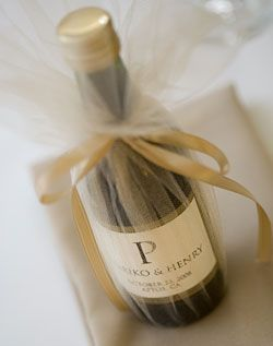 Mini champagne bottles wrapped in tulle with a gold ribbon-wedding favor idea