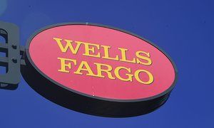 "A Wells Fargo sign is seen in front of a branch in Pasadena, California on September 28, 2016. Wells Fargo CEO John Stumpf will forgo USD 41 million in compensation, the bank's board of directors announced, as punishment for a bogus accounts scandal that has rocked the company. The California Treasurer John Chiang has said the state will suspend several banking relationships with Wells Fargo (WFC) to sanction the firm following allegations of ""fleecing its customers."" / AFP PHOTO / Frederic…"
