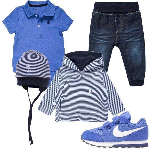 Outfit pensato per un nuovo arrivato formato da un body con colletto modello polo a maniche corte color blu reale, un jeans a sigaretta blu scuro e un cardigan a righe. Anche il berretto è a righe, mentre le sneakers sono in blu con chiusura in velcro.