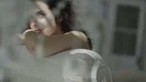 Beautiful brunette model in black lingerie relaxes in her boudoir with sunlight…