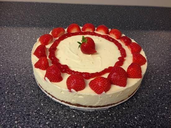 Witte Chocolade Strawberry Cheesecake recept / - 200 gram Bastognekoeken - 100 gram boter - 250 ml slagroom - 200 gram roomkaas (bv monchou), op kamertemperatuur - 250 gram mascarpone - 65 gram suiker - Merg van 1 vanillestokje of 1 zakje vanillesuiker - 500 gram witte chocolade - 400 gram aardbeien
