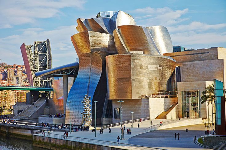 The Guggenheim's satellite in Bilbao, Spain, multiplied the museum's exhibition space in a mountain of stone, glass, and titanium that follows the contours of the Nervión river