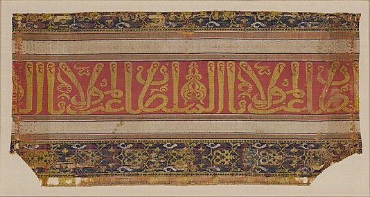 "Silk, lampas fragment; late 14th–early 15th century, Spain; The Metropolitan Museum of Art, Rogers Fund, 1918. This textile with a calligraphic band is an example of a ""tiraz"" (embroidery). The center band has a red background with the inscription ""Glory to our Lord the Sultan"" repeated in gold letters. The fragment is full of decorative elements, and the calligraphy is an example of the ""Thuluth"" style."