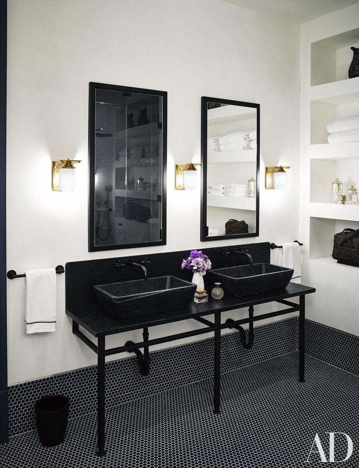 A black and white master bathroom with custom black sinks | archdigest.com