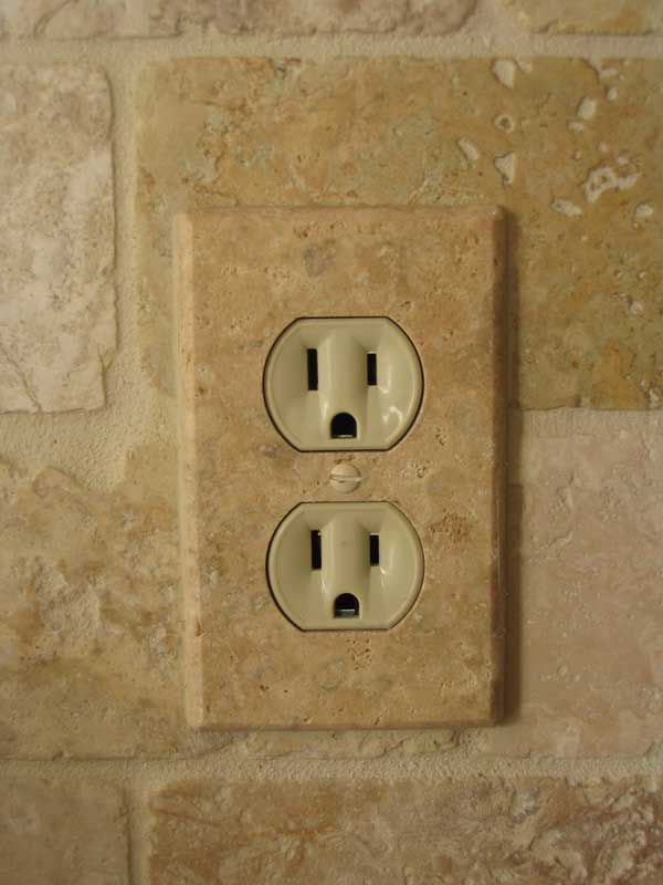 Installed travetine outlet cover plate