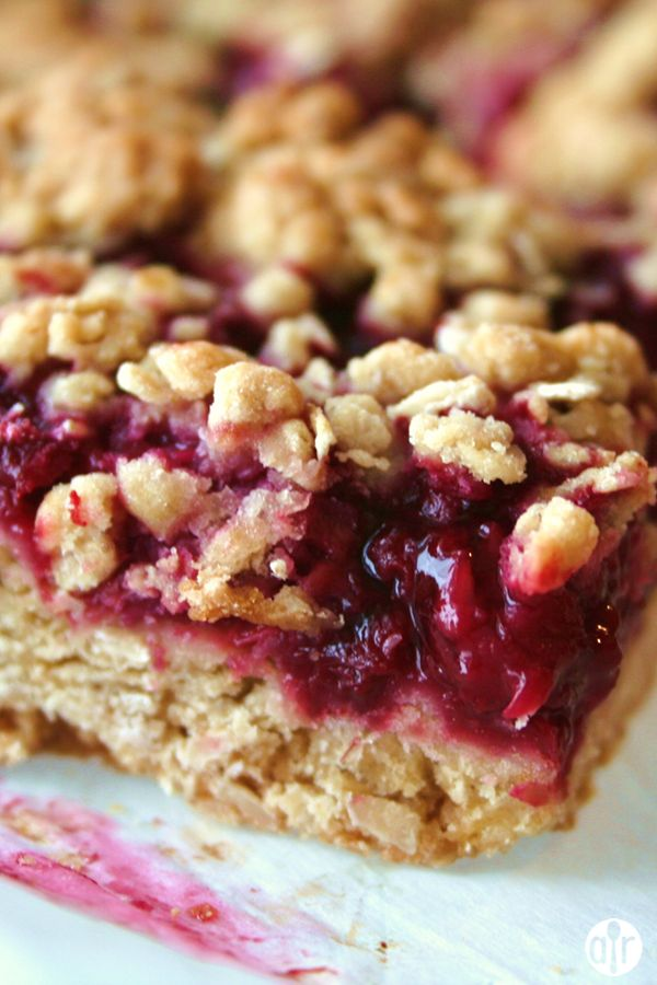 Delicious Raspberry Oatmeal Cookie Bars | Seedless raspberry jam is sandwiched between buttery brown sugar-oatmeal cookie crusts.