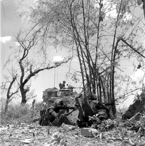 """""""Marine riflemen of the Ninth Marine Regiment combine fire power with a tank as they engage a well dug-in North Vietnamese Army unit north of Dong Ha. The Marines encountered the enemy while participating in Operation Kentucky in the northernmost area of South Vietnam."""" (1968)"""