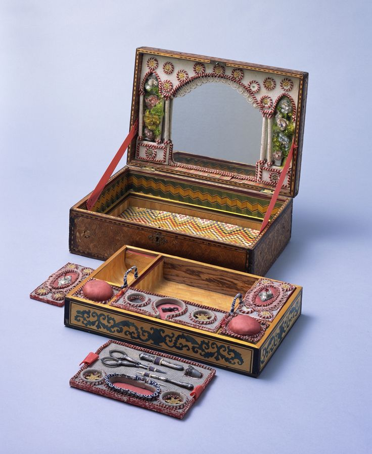 A beautiful parquet sewing box from the late 18th century featuring straw appliqué with geometric motifs and an arabesque design. The inner box is separated into six lidded compartments.