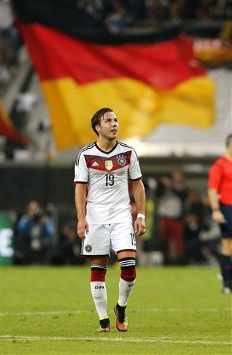 Germany's Mario Goetze walks in front of a German flag during the friendly soccer match between Germany and Argentina in Duesseldorf, Germany, Wednesday, Sept. 3, 2014.