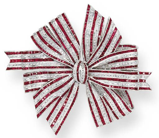 A RUBY AND DIAMOND BOW BROOCH   The ribbon bow set with alternating lines of calibré-cut rubies and circular-cut diamonds, mounted in platinum  The total weight of the rubies and diamonds is approximately 30.00 and 3.80 carats