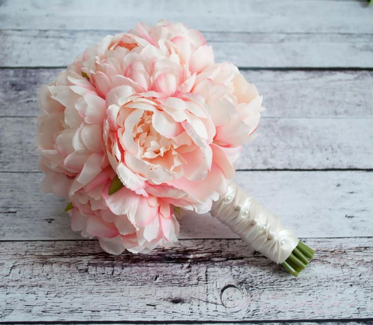 A blush pink peony bouquet for a bride or bridesmaid! Soft blush pink peonies are tied with ivory satin and pearl pin accents. This bouquet measures 8 inches wide and 10 inches tall. Coordinating larg