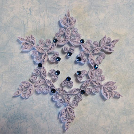 This quilled snowflake ornament is about 4 1/4 in diameter. The white paper strips are made from pearl paper; so when the light hits it just