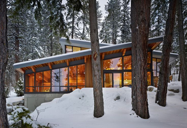 16 Examples Of Modern Houses With A Sloped Roof | This modern lake house has multiple sloped roofs to allow the rain and snow slide off.