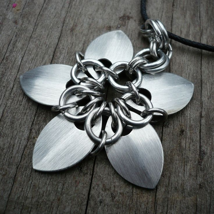 Dračí šupiny silver - přívěsek Přívěsek ve tvaru květiny z hliníkovách šupin a hliníkových eloxovaných kroužků. Průměr květinky cca 5 cm.Přívěsek je na černé voskované šňůrce, zapínání karabinka. Délka šňůrky 45 cm+ prodlužující řetízek.
