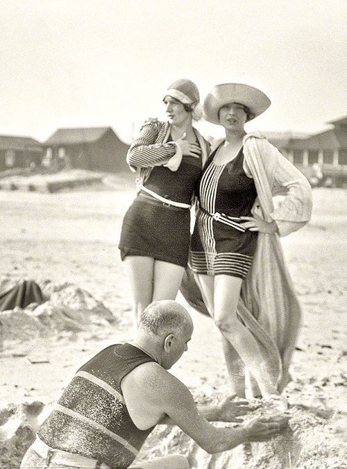 librar-y:  Circa 1925. Man building sand castle and two unidentified women. Long Beach, New York.