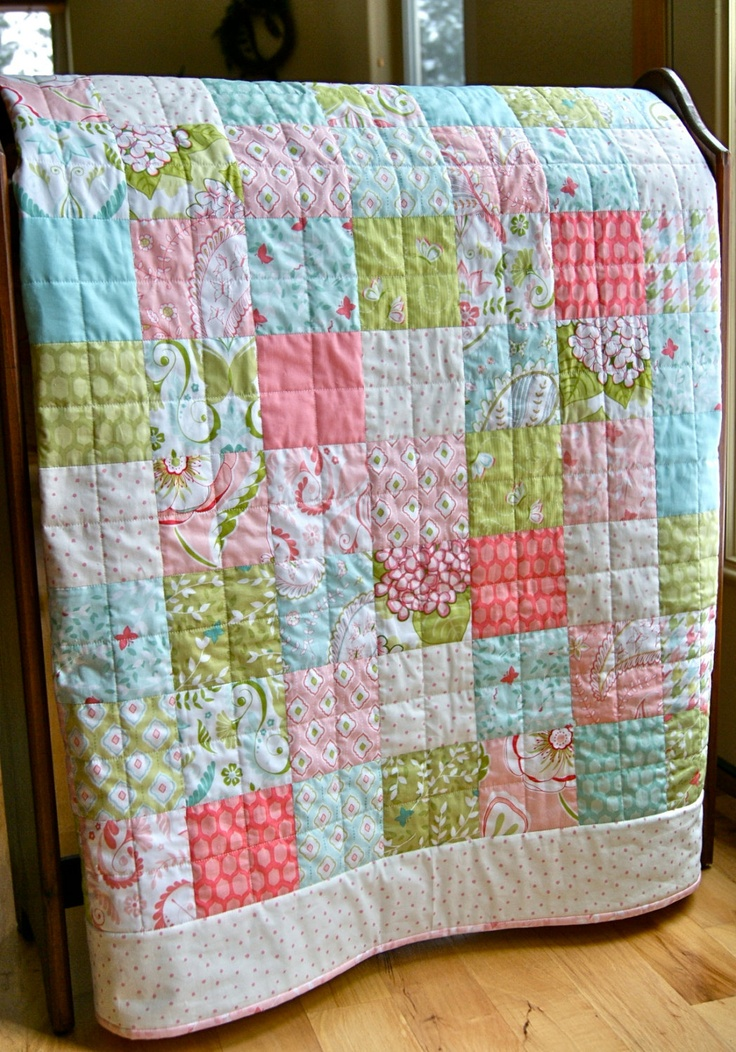 "Handmade quilt with fresh, pretty fabrics called Bella Butterfly by Patty Sloniger. Squares of pink, blue, green and white are pieced together in a classic patchwork design and bordered with a tiny pink and white dot. The quilt measures 43 1/2"" x 50 1/2"". The quilting is straight lines of quilting in the seams and across each square with white cotton thread. This type of quilting results in a very soft, fluffy and so cuddly quilt! Stiched by Janet of Pine, Colorado (Pieces of Pine on Etsy)…"