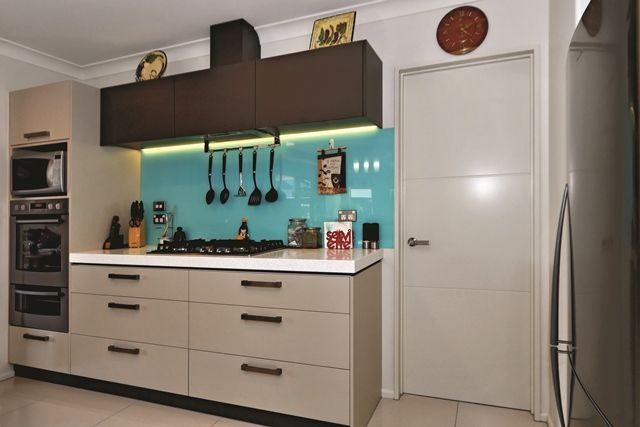 The home boasts an immaculate kitchen with bright aqua splashback.