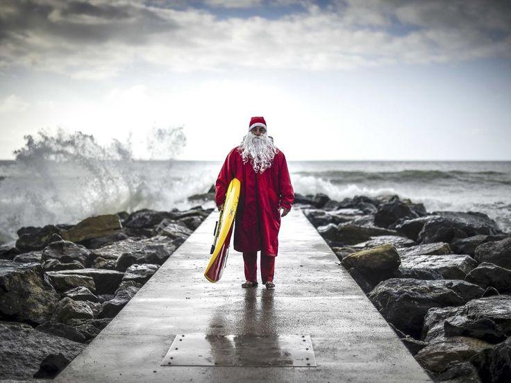 Italian Stand up Paddle surfer Federico Piccinaglia dressed as Santa Claus poses with his board in Levanto, near La Spezia.