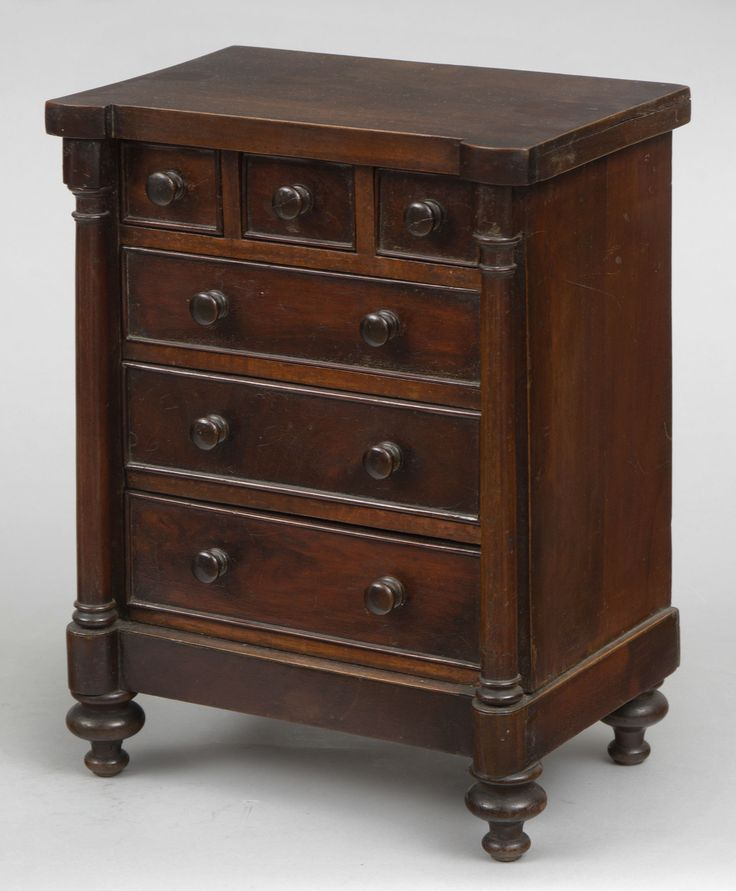 English miniature mahogany chest of drawers with shaped top, open columns flanking three short and three long cock-beaded graduated drawers, mahogany knobs, raised on turnip-shaped feet.      English Circa 1830     Height: 13.5"