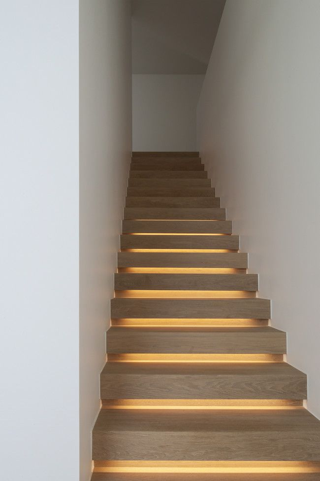 Wood staircase with lighting that creates a soft glow by using lighting strips.