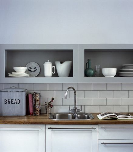 Dark wooden counter top, white subway tiles with grey grout, stainless steel. Very nice. I like the door and drawer pulls, too.