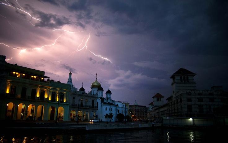 Raio ilumina a via do Malecón em Havana, capital cubana, na noite de quarta-feira (19).
