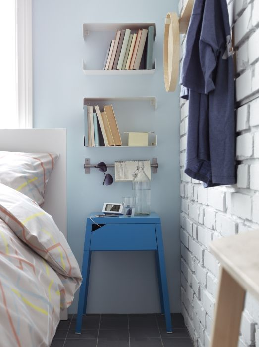 If you need more space to place things than a small nightstand can offer, make smart use of wall space with shelves and rails.